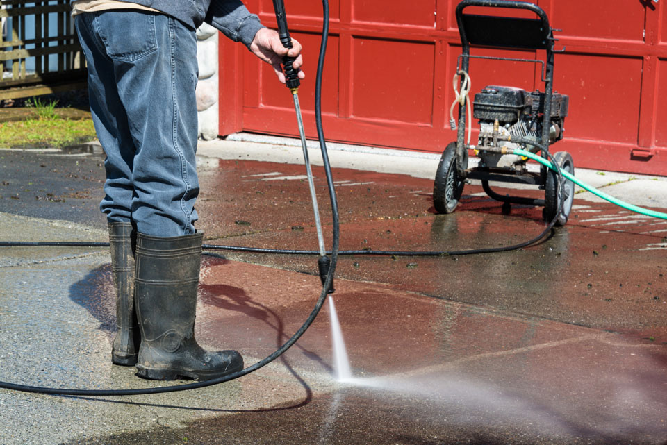 Man cleaning driveway with portable pressure power washer